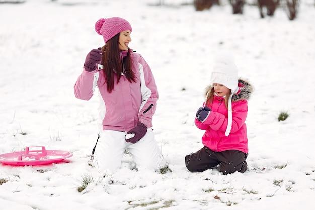 Família em chapéus de malha de inverno nas férias de natal em família. mulher e menina em um parque. pessoas brincando.
