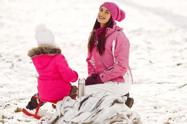 Família em chapéus de malha de inverno nas férias de natal em família. mulher e menina em um parque. pessoas com garrafa térmica.