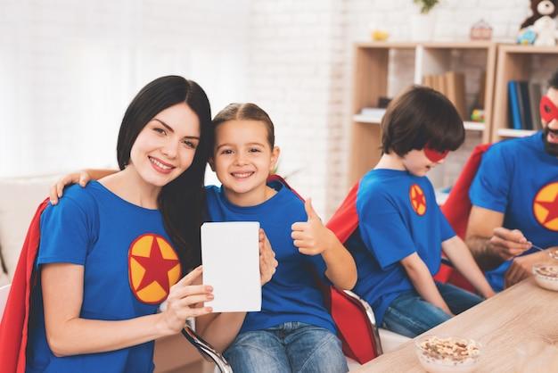Família em fantasias de super-heróis, comendo em casa.