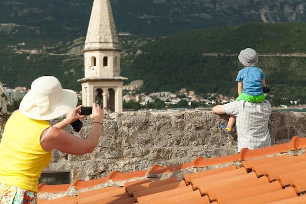 Família em férias com a mãe fotografando o filho e o marido com uma câmera digital em viagem para a europa