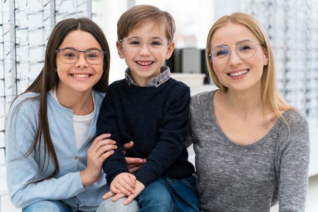Família em loja de óculos experimentando