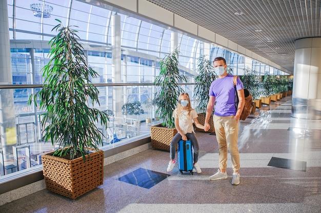 Família em máscara médica facial no aeroporto.
