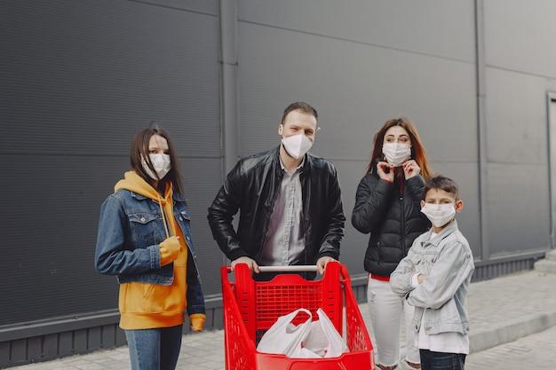 Família em máscaras protetoras com compras