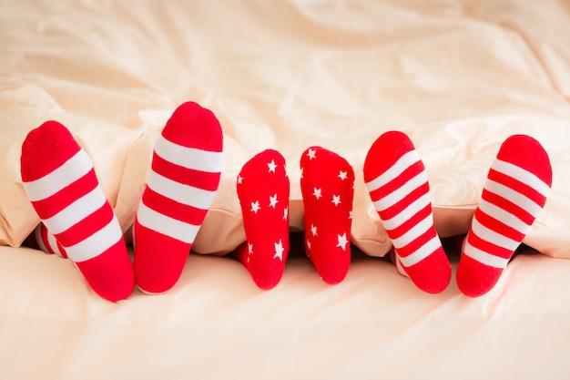 Família em meias de natal, deitada na cama. mãe, pai e bebê se divertindo juntos