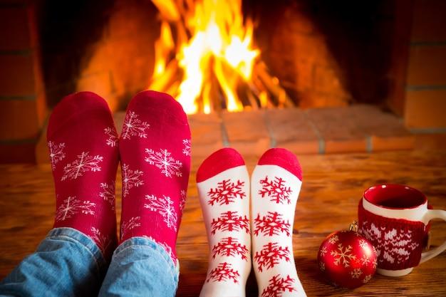 Família em meias de natal perto da lareira. mãe; pai e bebê se divertindo juntos. pessoas relaxando em casa