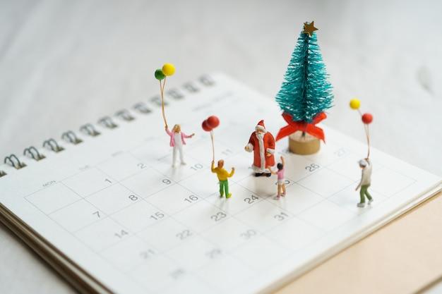 Família em miniatura em pé na árvore de natal comemore o natal