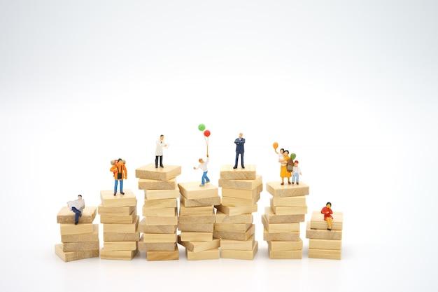 Família em miniatura em pé na pilha de papéis