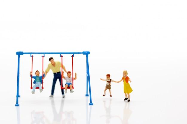Família em miniatura, jogando no balanço
