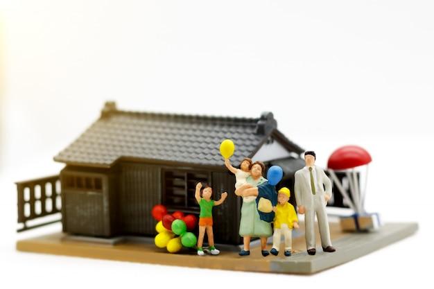 Família em miniatura na frente da casa