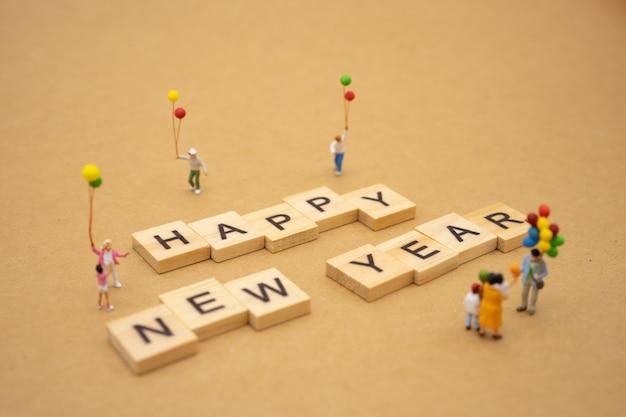 Família em miniatura pessoas em pé com a palavra madeira feliz ano novo