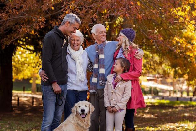 Família em pé com cachorro no parque