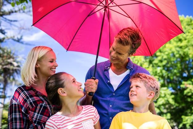 Família em pé sob o guarda-chuva
