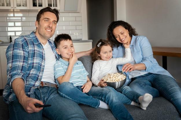 Família em plano médio assistindo televisão