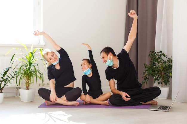 Família em roupas esportivas, assistindo a vídeos online no laptop e fazendo exercícios de fitness em casa. treinamento à distância com personal trainer, distância social ou auto-isolamento, conceito de educação online