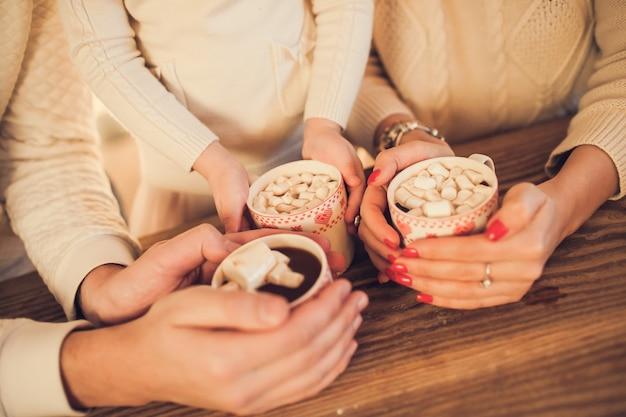 Família em suéteres brancos cozinha e bebe chocolate com marshmallows