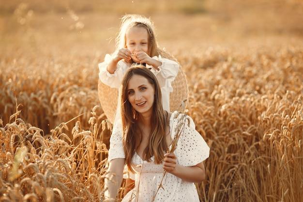 Família em um campo de trigo. mulher de vestido branco. menina com chapéu de palha.