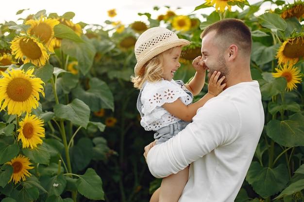 Família em um campo de verão com girassóis. pai em uma camisa branca. criança fofa.