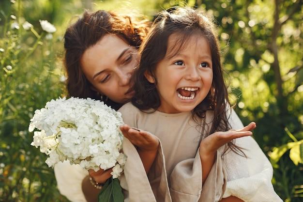 Família em um jardim de verão. foto sensual. menina bonitinha. mulher com buquê.