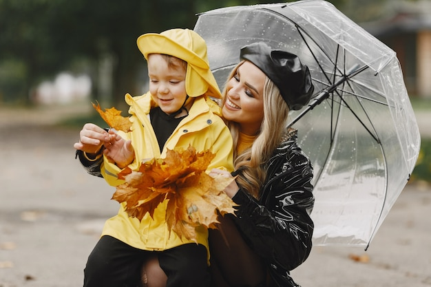 Família em um parque chuvoso. garoto com uma capa de chuva amarela e mulher com um casaco preto.