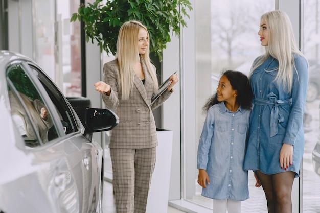 Família em um salão de automóveis. mulher comprando o carro. menina africana com mther. gerente com clientes.