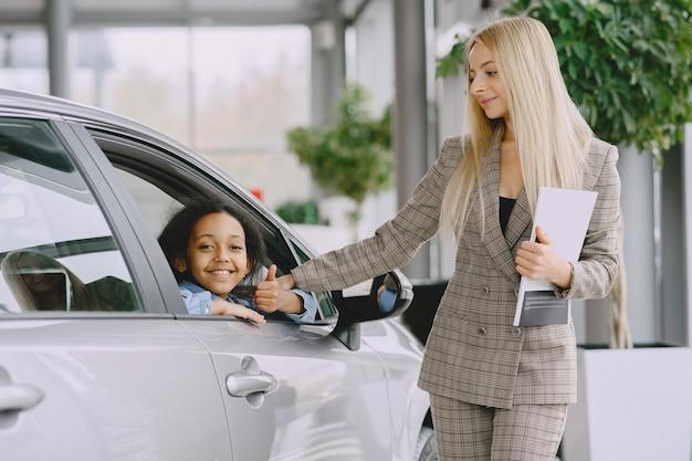 Família em um salão de automóveis. mulher comprando o carro. menina africana com mther.