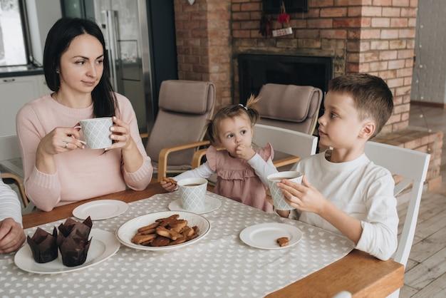 Família em uma casa grande. estilo de vida conforto em casa. crianças em casa. linda cozinha. dieta infantil. família almoça juntos. biscoito de gengibre com chá. lareira de tijolo vermelho. mesa de jantar grande