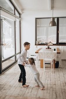 Família em uma casa grande. estilo de vida conforto em casa. crianças em casa. linda cozinha. irmão e irmã brincam na cozinha. janelas no chão. janelas enormes.