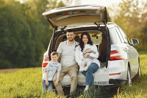 Família em uma floresta de verão pelo porta-malas aberto