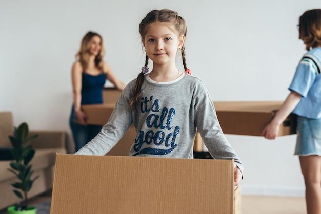 Família embalando caixas na nova casa no dia da mudança.