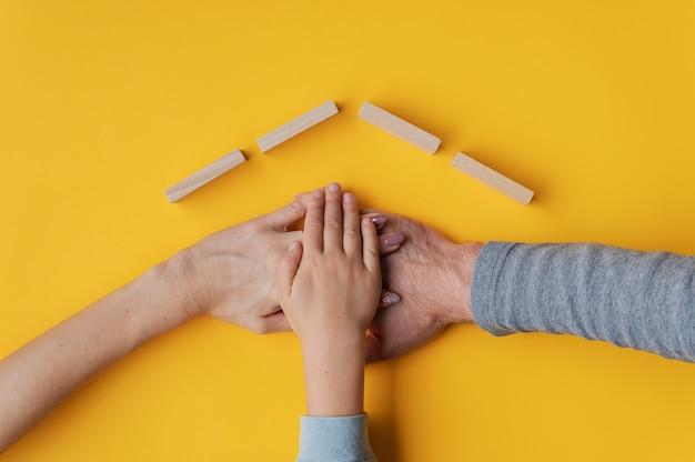Família empilhando a mão na parede amarela com telhado feito de blocos de madeira acima de suas mãos em uma imagem conceitual de casa própria e segurança.