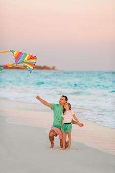 Família empinando pipa juntos na praia branca tropical