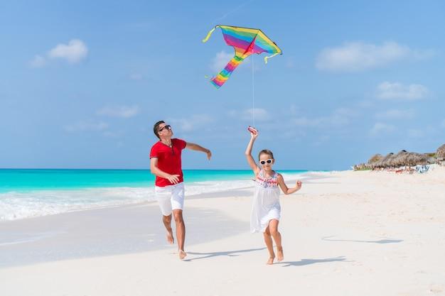 Família empinando pipa juntos na praia tropical branca