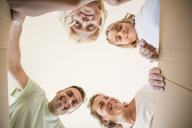 Família encantada com crianças fofas abrindo uma caixa de papelão em movimento e olhando dentro