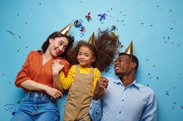 Família engraçada em bonés comemora aniversário, fundo azul. menina bonita e seus pais, celebração do evento, decoração de balões e confetes
