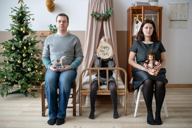 Família engraçada ridícula com as caras sérias que sentam-se no estúdio com árvore dos cristmas.