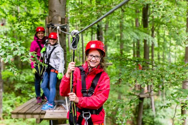 Família escalando em curso de corda alta