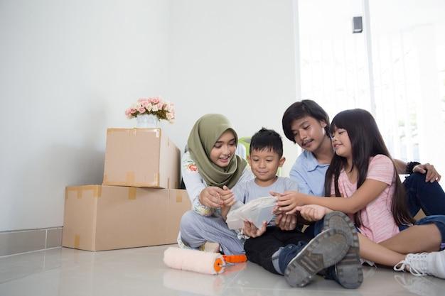 Família escolhendo tinta colorida para sua nova casa