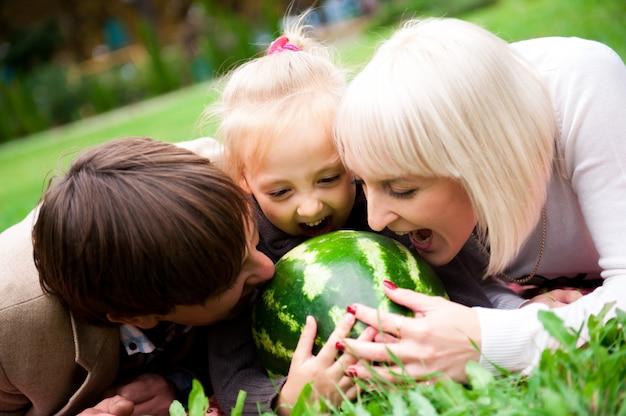Família está comendo uma melancia juntos no parque.