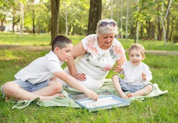 Família estendida alegre jogando jogo de tabuleiro em seu quintal.
