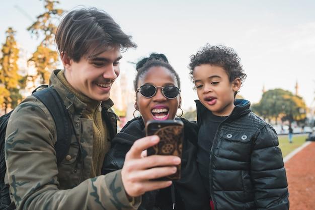 Família étnica de raça mista, tendo selfie.
