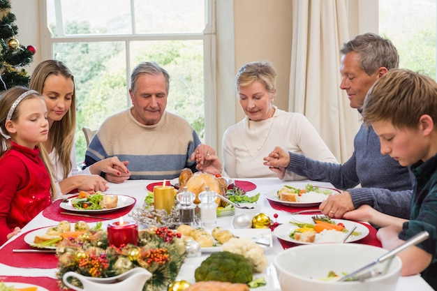 Família extensa dizendo graça antes do jantar de natal