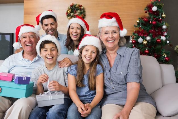 Família extensa em chapéus de natal com caixas de presente na sala de estar