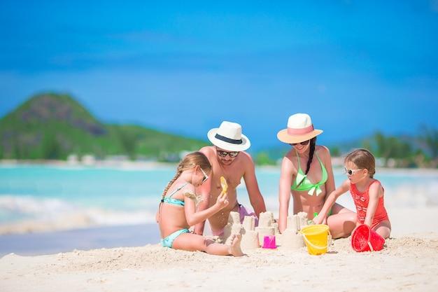 Família fazendo castelo de areia na praia branca tropical