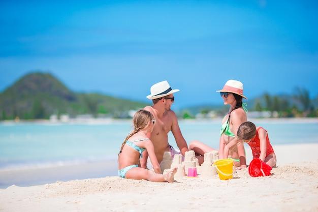 Família fazendo castelo de areia na praia tropical branca