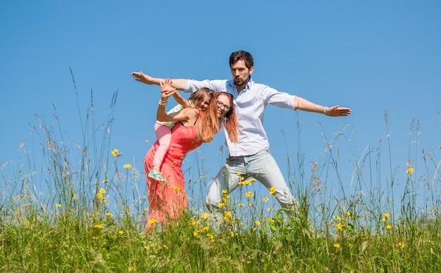 Família fazendo o avião em um prado de verão sob um céu azul claro