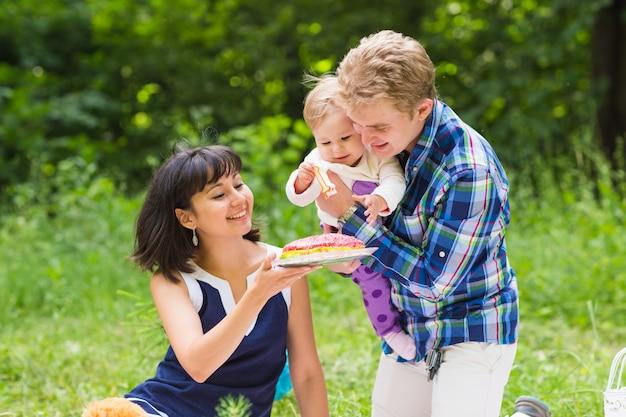 Família fazendo piquenique ao ar livre com sua linda filha.