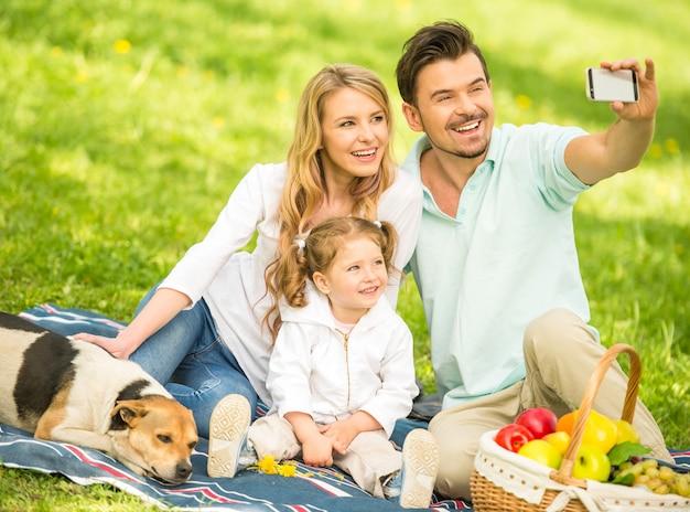 Família fazendo piquenique ao ar livre e fazendo selfie.
