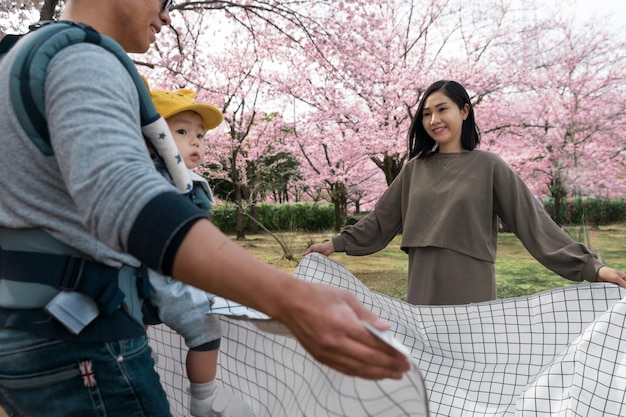 Família fazendo piquenique ao lado de uma cerejeira