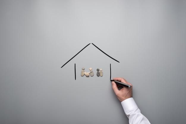Família feita de pedras em uma casa de mão desenhada