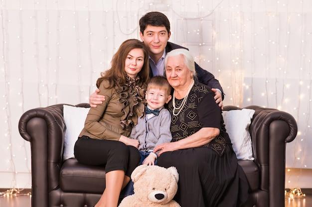 Família, felicidade, geração e conceito dos povos - família feliz que senta-se no sofá em casa